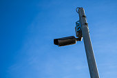 Weathered surveillance camera outside for a blue sky