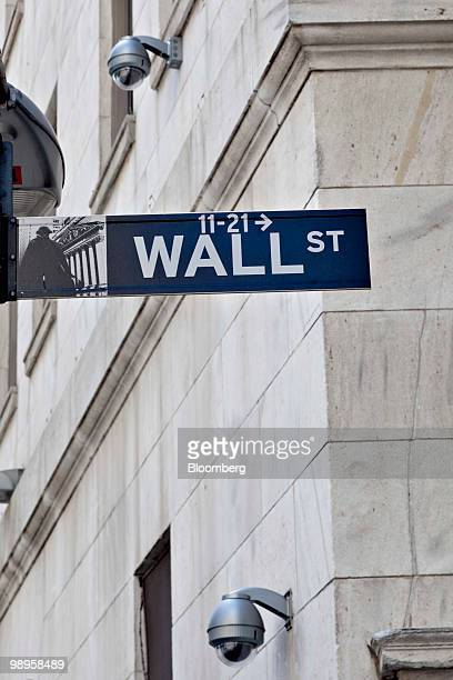 Security cameras hang on the exterior of the New York Stock Exchange in the background of a Wall Street sign in New York US on Monday May 10 2010...