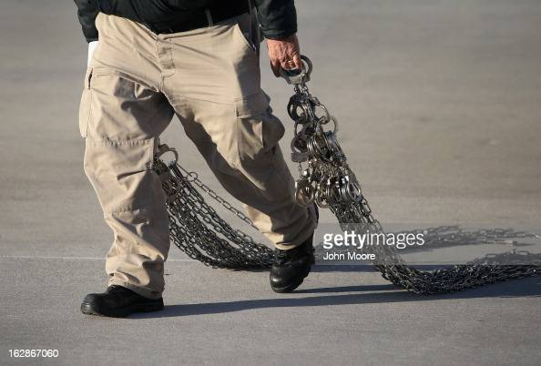 A security contractor carries chains for immigration detainees from Honduras ahead of a deportation flight to San Pedro Sula Honduras on February 28...
