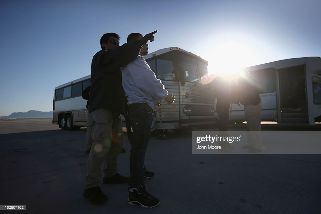 A security contractor hired by U.S. Immigration and Customs Enforcement (ICE), points a Honduran immigration detainee towards a deportation flight bound for San Pedro Sula, Honduras on February 28, 2013 in Mesa, Arizona. ICE operates 4-5 flights per week from Mesa to Central America, deporting hundreds of undocumented immigrants detained in western states of the U.S. With the possibility of federal budget sequestration, ICE released 303 immigration detainees in the last week from detention centers throughout Arizona. More than 2,000 immigration detainees remain in ICE custody in the state. Most detainees typically remain in custody for several weeks before they are deported to their home country, while others remain for longer periods while their immigration cases work through the courts.