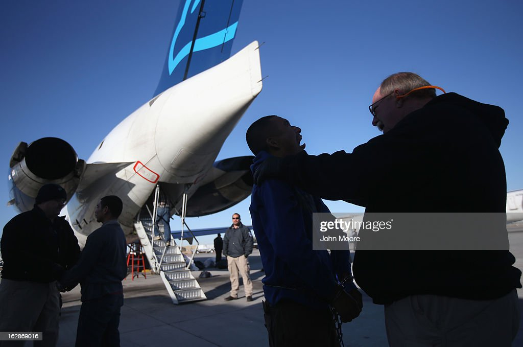 A security contractor hired by U.S. Immigration and Customs Enforcement (ICE), checks the mouth of a Honduran immigration detainee from Honduras before a deportation flight to San Pedro Sula, Honduras on February 28, 2013 in Mesa, Arizona. ICE operates 4-5 flights per week from Mesa to Central America, deporting hundreds of undocumented immigrants detained in western states of the U.S. With the possibility of federal budget sequestration, ICE released 303 immigration detainees in the last week from detention centers throughout Arizona. More than 2,000 immigration detainees remain in ICE custody in the state. Most detainees typically remain in custody for several weeks before they are deported to their home country, while others remain for longer periods while their immigration cases work through the courts.