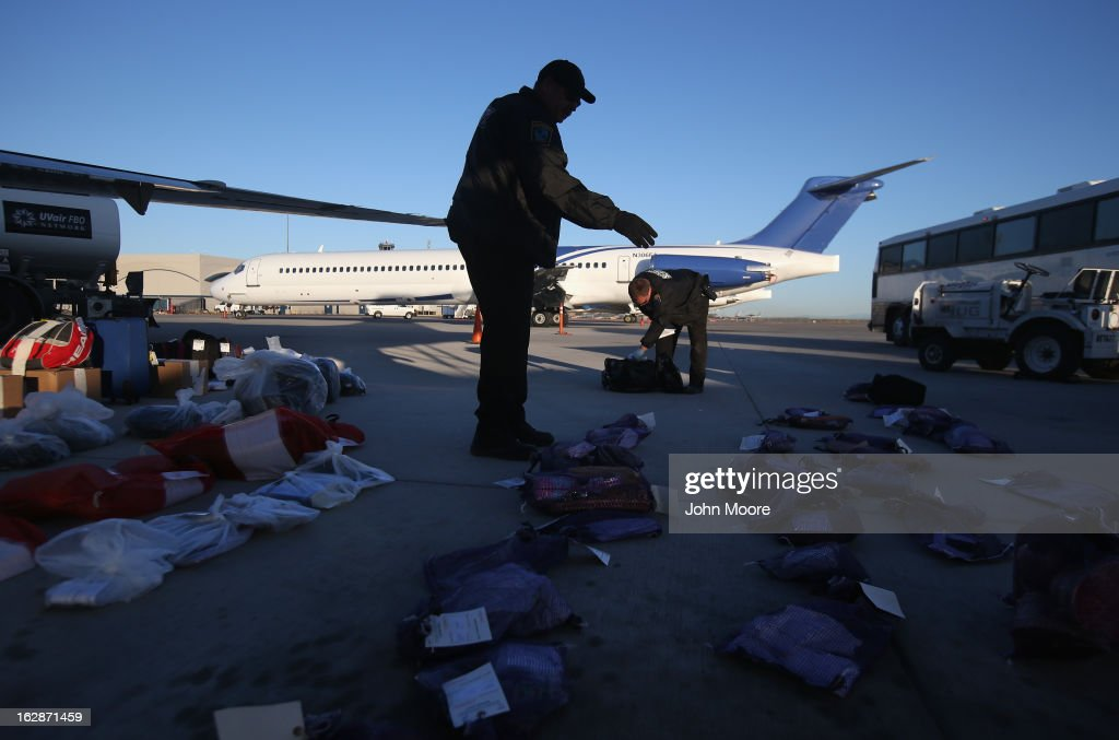 A security contractor hired by U.S. Immigration and Customs Enforcement (ICE), counts bags of personal possessions of Honduran immigration detainees before their deportation flight bound for San Pedro Sula, Honduras on February 28, 2013 in Mesa, Arizona. ICE operates 4-5 flights per week from Mesa to Central America, deporting hundreds of undocumented immigrants detained in western states of the U.S. With the possibility of federal budget sequestration, ICE released 303 immigration detainees in the last week from detention centers throughout Arizona. More than 2,000 immigration detainees remain in ICE custody in the state. Most detainees typically remain in custody for several weeks before they are deported to their home country, while others remain for longer periods while their immigration cases work through the courts.