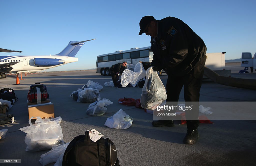 A security contractor hired by U.S. Immigration and Customs Enforcement (ICE), lays out personal possessions of Honduran immigration detainees before their deportation flight bound for San Pedro Sula, Honduras on February 28, 2013 in Mesa, Arizona. ICE operates 4-5 flights per week from Mesa to Central America, deporting hundreds of undocumented immigrants detained in western states of the U.S. With the possibility of federal budget sequestration, ICE released 303 immigration detainees in the last week from detention centers throughout Arizona. More than 2,000 immigration detainees remain in ICE custody in the state. Most detainees typically remain in custody for several weeks before they are deported to their home country, while others remain for longer periods while their immigration cases work through the courts.