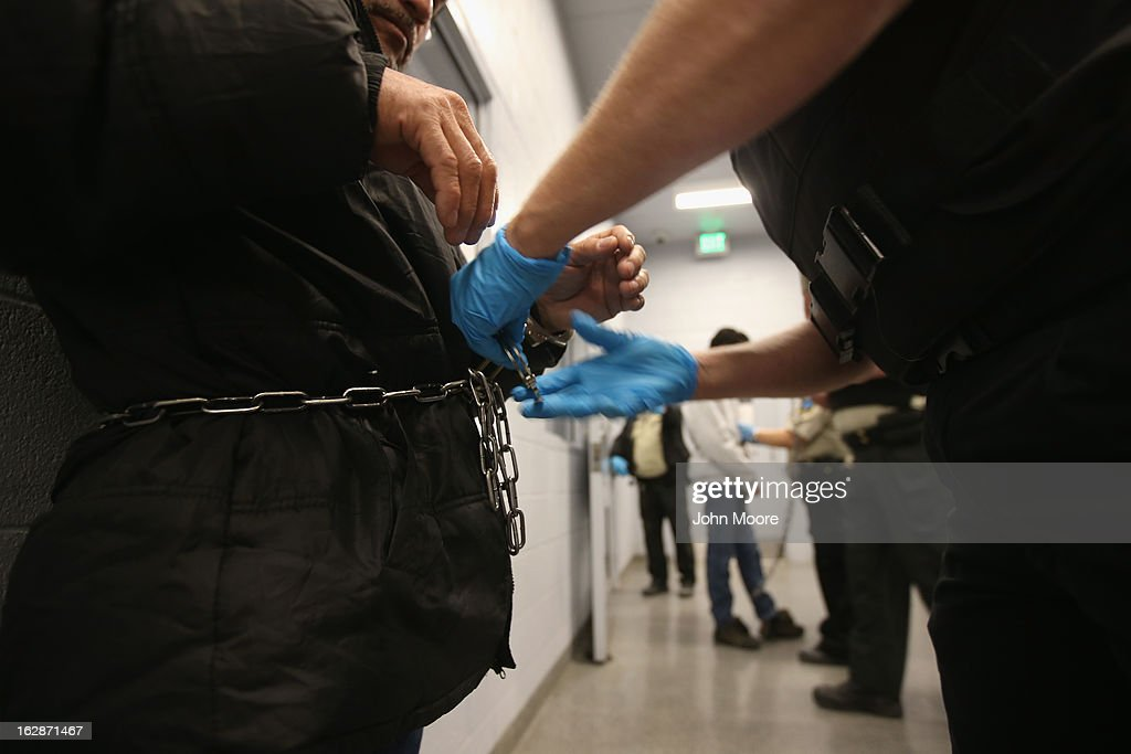 A security contractor hired by U.S. Immigration and Customs Enforcement (ICE), chains Honduran immigration detainees before their deportation flight bound for San Pedro Sula, Honduras on February 28, 2013 in Mesa, Arizona. ICE operates 4-5 flights per week from Mesa to Central America, deporting hundreds of undocumented immigrants detained in western states of the U.S. With the possibility of federal budget sequestration, ICE released 303 immigration detainees in the last week from detention centers throughout Arizona. More than 2,000 immigration detainees remain in ICE custody in the state. Most detainees typically remain in custody for several weeks before they are deported to their home country, while others remain for longer periods while their immigration cases work through the courts.