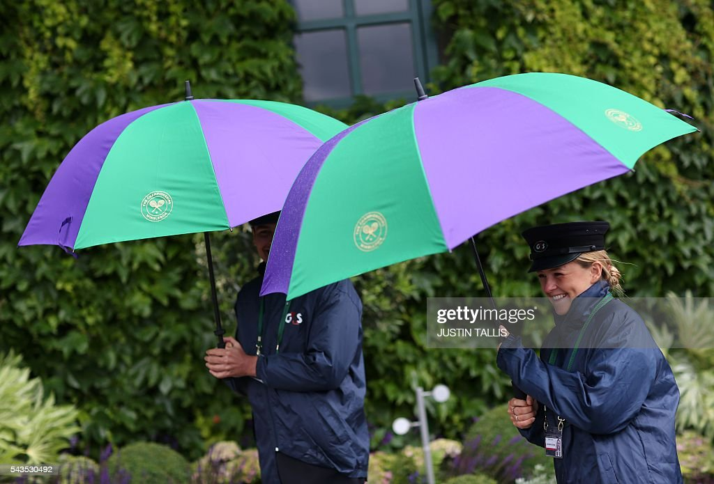 Security contractors shelter under umbrellas on the rain delayed third day of the 2016 Wimbledon Championships at The All England Lawn Tennis Club in Wimbledon, southwest London, on June 29, 2016. / AFP / JUSTIN