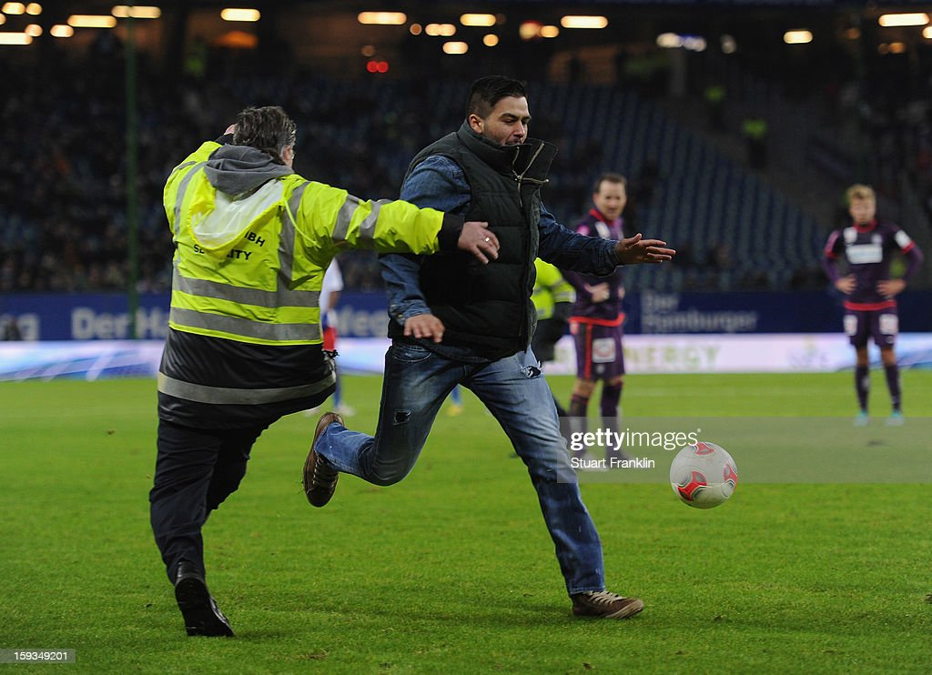 Security control a fan who ran onto the pitch during the international friendly match between Hamburger SV and Austria Wien at Imtech Arena on January 12, 2013 in Hamburg, Germany.