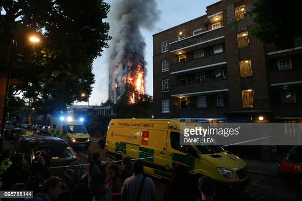 TOPSHOT A security cordon holds people backs as Grenfell Tower is engulfed by fire on June 14 2017 in west London The massive fire ripped through the...