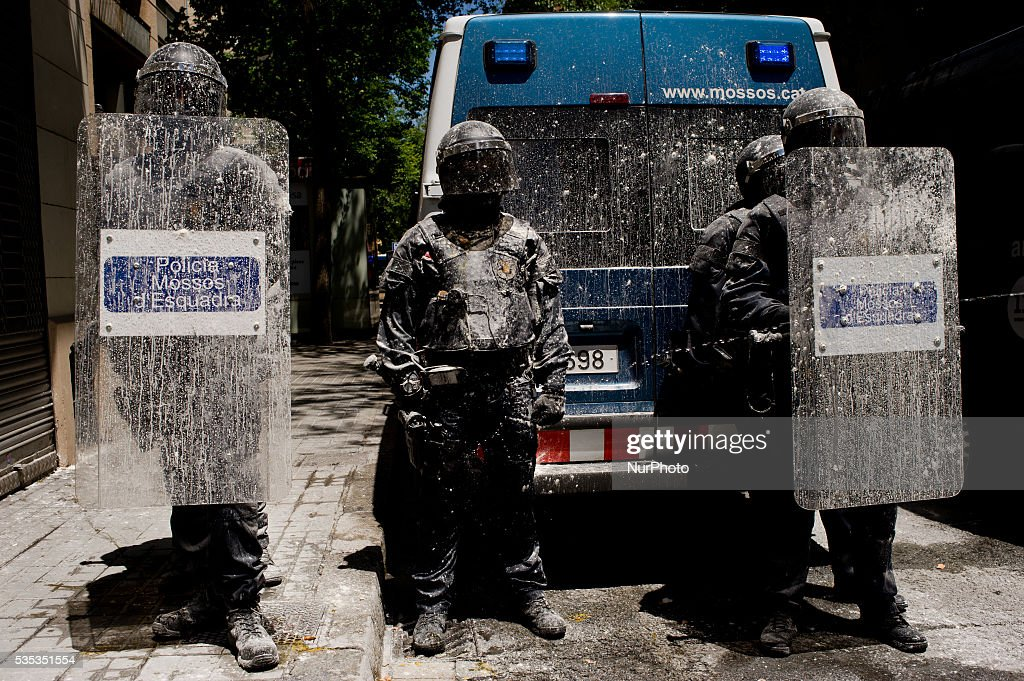 A security cordon of riot police officers stained by water and flour thrown by protesters in the streets of Barcelona (Spain) on May 29, 2016. Tense Sunday in the streets of the popular Gracia district of Barcelona. After the eviction of an occupied bank branch known as the Banc Expropiat (Expropiated Bank) on past Monday 23 riots have been happening following days. Today hundreds of protesters tried to enter the building again guarded by riot police officers.