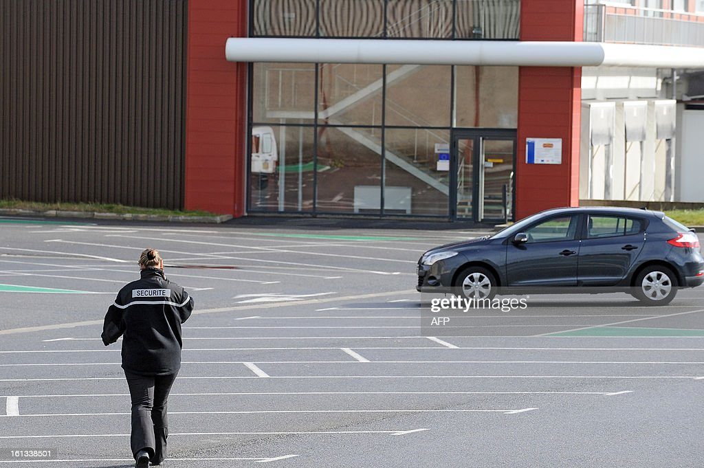 A security employee walks on the parking lots area of the French meat food industrial factory Spanghero head quarters in Castelnaudary, southeastern France, on February 10, 2013. A Europe-wide food fraud scandal over horsemeat sold as beef deepened on February 9, 2013 as Romania announced an inquiry into the origin of the meat and suspicions of criminal activity mounted. AFP PHOTO REMY GABALDA