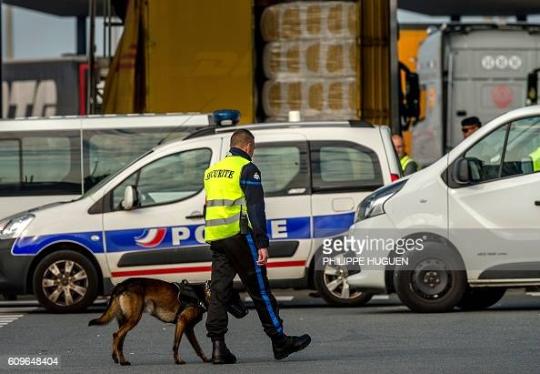 A security employee walks with a dog at the ferry terminal of the port of Calais on September 21 2016 / AFP / PHILIPPE HUGUEN