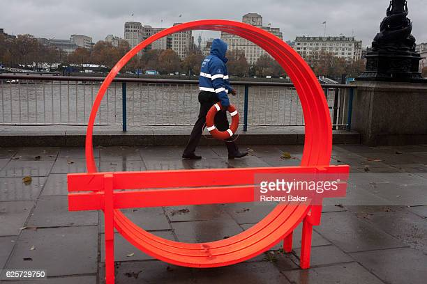A security employee working for London's Southbank carries a life ring coincidentally passing through circular artwork overlooking the River Thames...