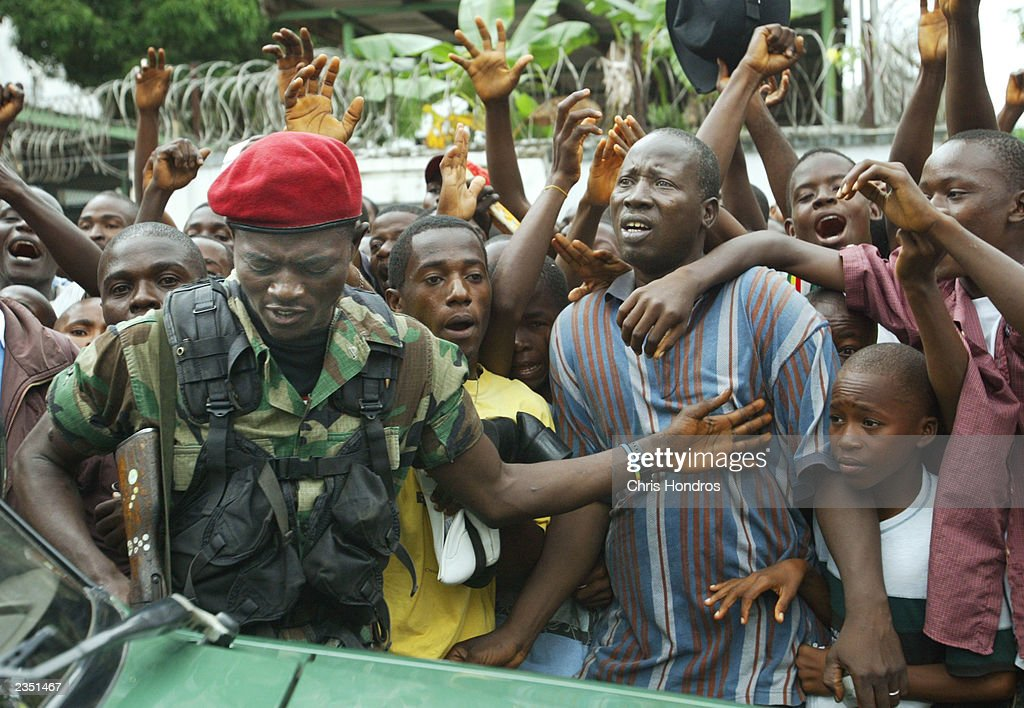 Security for a group of Nigerian officers sent to evaluate peacekeeping options brushes aside people as he gets into the motorcade July 31, 2003 in Monrovia, Liberia. The first group of Nigerian peacekeepers will hit the ground by August 4 officials said.