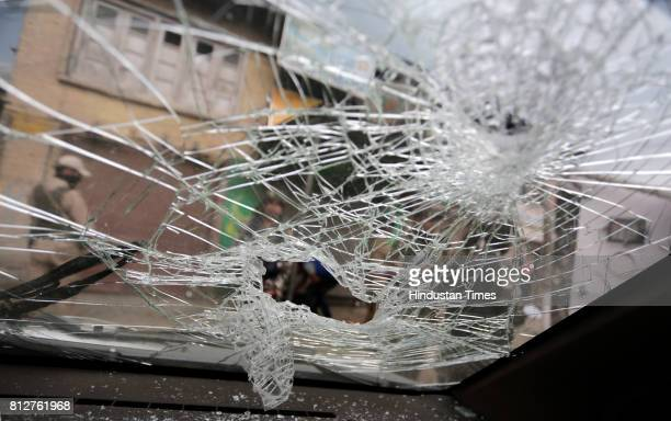 Security force personnel seen through a broken windshield of a private vehicle which was damaged at the site of militant attack on July 11 2017 in...