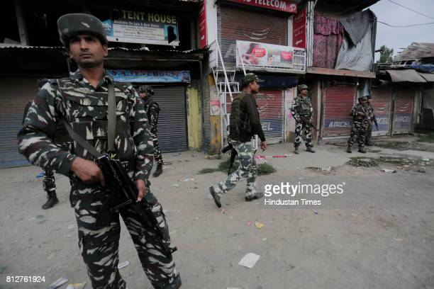 Security force personnel stand guard at the site of a militant attack on July 11 2017 in Batengo village around 40 kilometers south of Srinagar India...