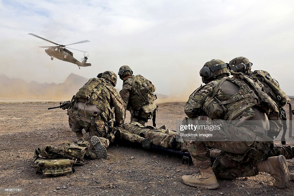 Security force team members wait for a UH-60 Blackhawk medevac helicopter.