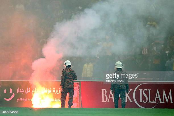 Security forces and Policemen moves in after Malaysian fans sets fire bombs and rockets during the 88th minutes of the game during the 2018 Russia...