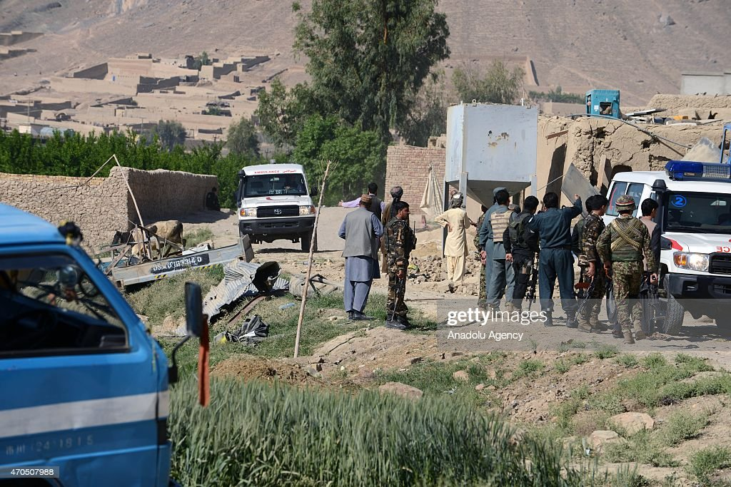 Security forces inspect the damage at the scene after a weapon's stockpile exploded at a checkpoint in Kandahar Afghanistan on April 21 2015 At least...