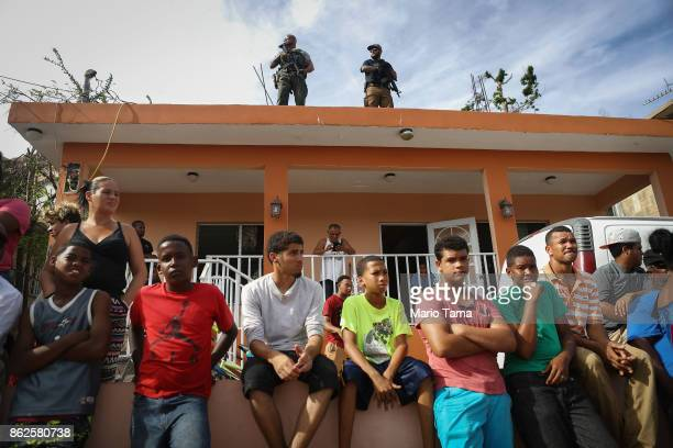 Security forces keep watch as residents gather and wait to receive food and water provided by FEMA in a neighborhood without grid electricity or...