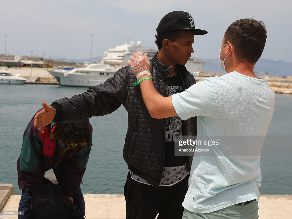A security forces member frisks a refugee after they were captured by coast guard while trying to pass illegally to Chios of Greek from Cesme in Izmir, Turkey on May 24, 2016. Turkish coast guard captured approximately 42 refugees after the operation.