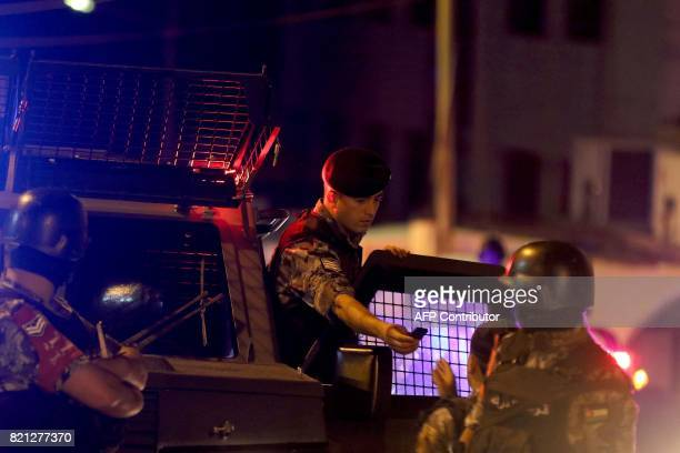 Security forces member speak as they stand guard outside the Israeli embassy in the residential Rabiyeh neighbourhood of the Jordanian capital Amman...