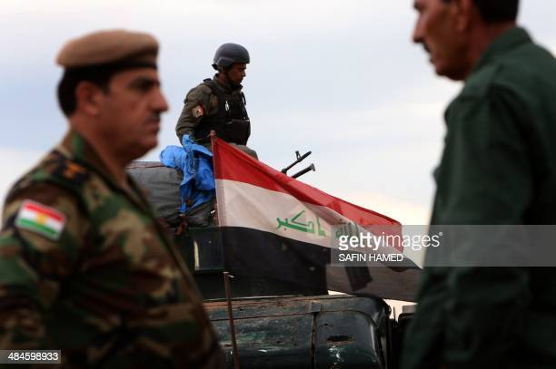 Security forces members stand guard during the digging operations to build a trench on the northern Iraqi border with Syria to prevent people from...