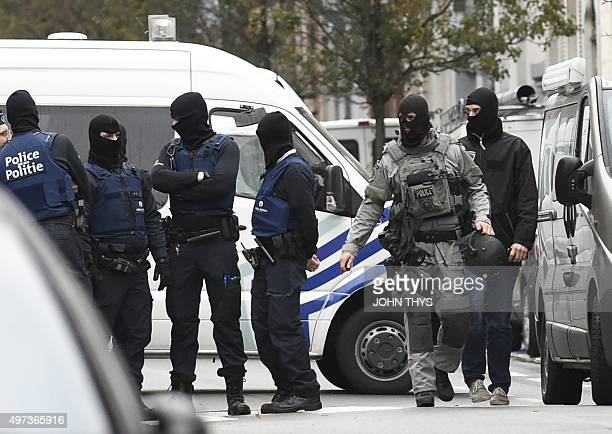 Security forces personnel walk past during ongoing operations in the Molenbeek district of Brussels on November 16 2015 Belgian police launched a...