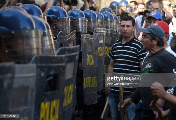 Security forces stand guard as farmers demonstrate to demand the writing off of their debts in downtown Asuncion on August 8 2017 Farmers are facing...