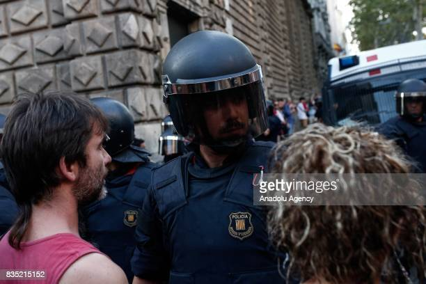 Security forces stand guard as representatives of Catalan organizations and people clash with a group of protesters who stage an anti Islamic protest...