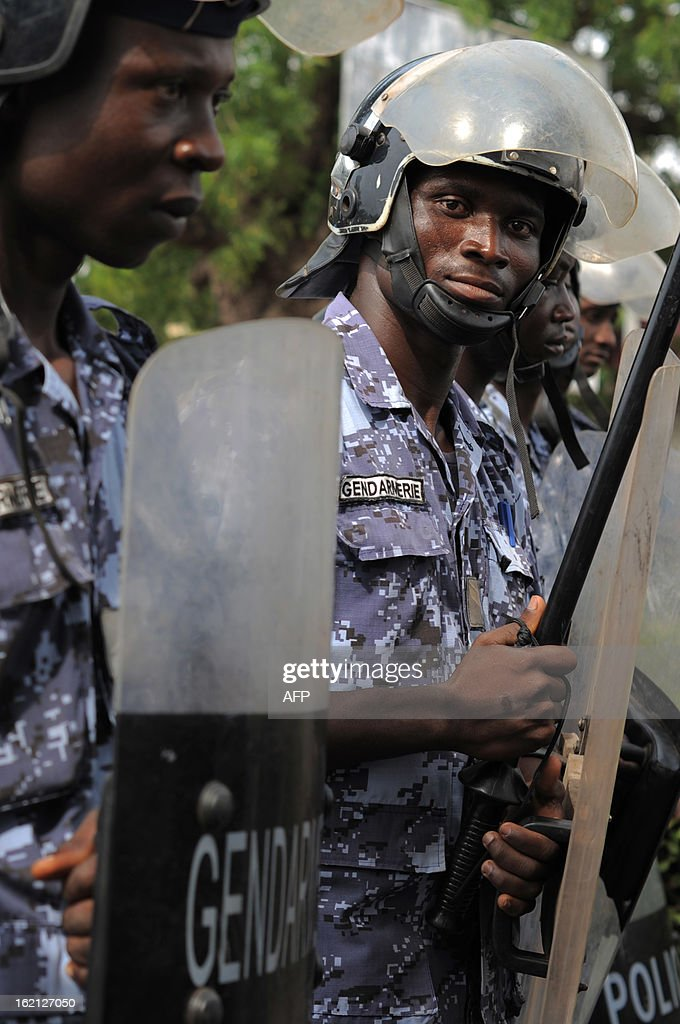 Security forces stand to prevent a crowd of several hundred journalists and members of the public from protesting in front of the Palais des Congres in Lome on February 19, 2013. Journalists in Togo are protesting against a law giving the High Authority of Audiovisual and Communication (HAAC) more power to control media in Togo.