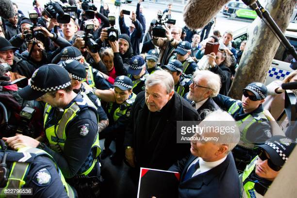 Security forces surround Cardinal George Pell as he arrives for court hearing at the Melbourne Magistrates Court in Melbourne Australia on July 26...
