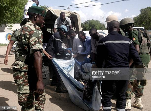 Security forces transport with a blanket the remains of some of the eleven victims of a double blast in the northern Cameroonian city of Maroua on...