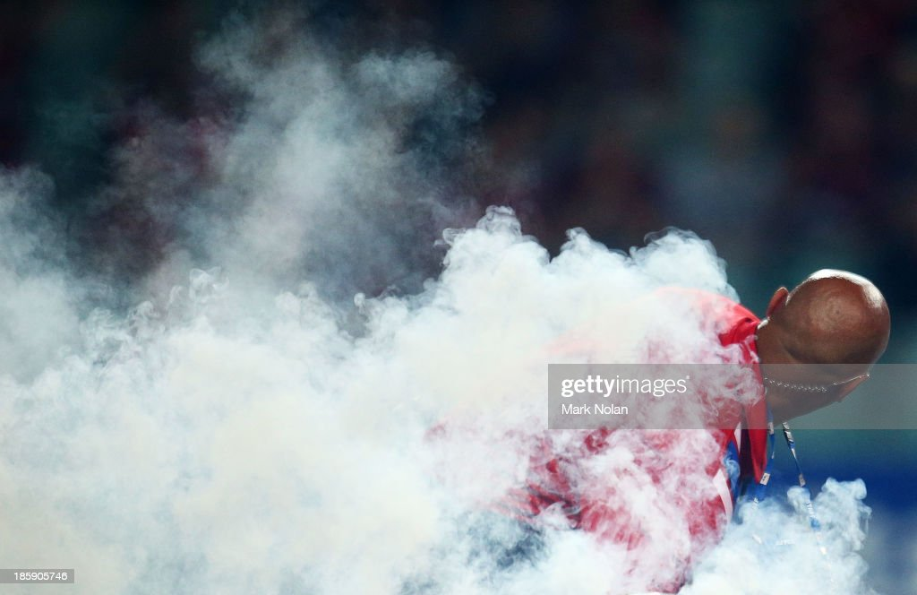 A security gaurd handles a flare during the round three A-League match between Sydney FC and the Western Sydney Wanderers at Allianz Stadium on October 26, 2013 in Sydney, Australia.