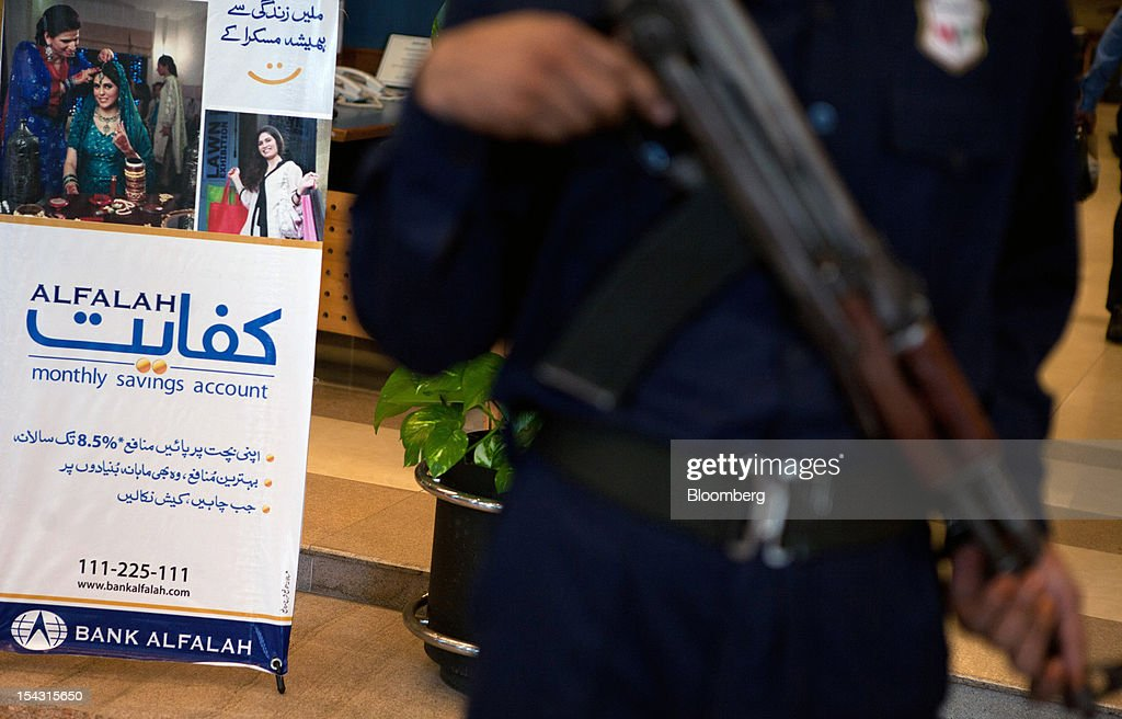 A security guard armed with a weapon stands inside a Bank Alfalah Ltd. branch in Karachi, Pakistan, on Wednesday, Oct. 17, 2012. Bank Alfalah, Pakistan's second-biggest Islamic lender, may see 20 percent growth in net income this year and in 2013 as it expands its branch network to tap growing demand for Shariah-compliant finance. Photographer: Asim Hafeez/Bloomberg via Getty Images