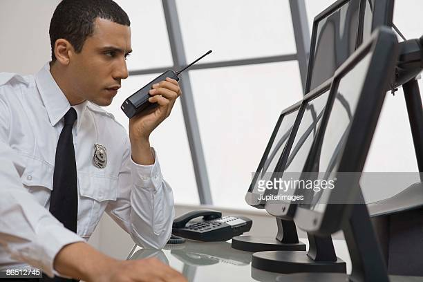 Security guard at desk with computer monitors