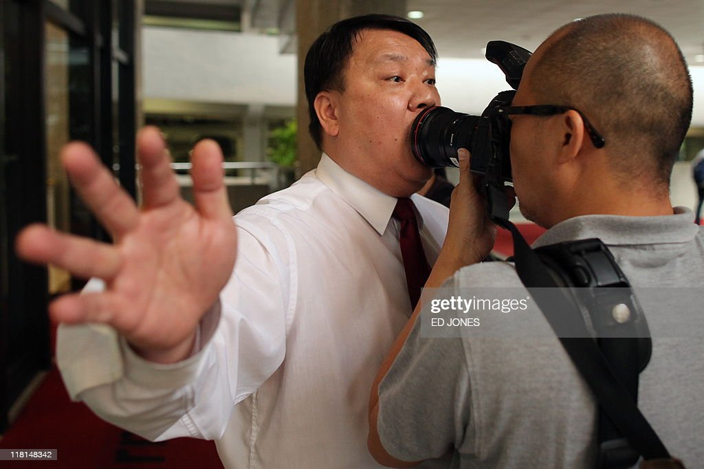 A security guard attempts to restrict a photographer from taking photos of a protest calling for the release of detained Thai human rights activist...