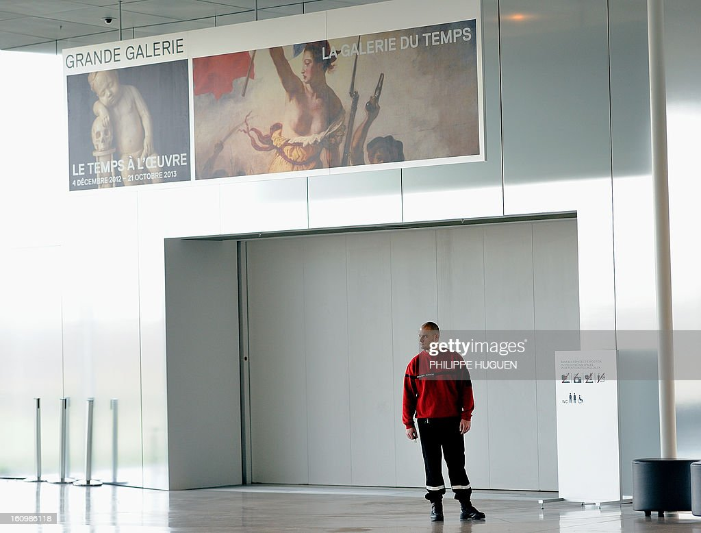 A security guard blocks the entrance of the 'Galerie du Temps' at the Louvre-Lens Museum in the French northern city of Lens, on February 8, 2013 after a woman vandalised on the eve the Eugene Delacroix masterpiece 'La Liberté guidant le Peuple' (Liberty leading the people, by writing on it 'AE911' with a black permanent marker on the painting. AFP PHOTO/ PHILIPPE HUGUEN