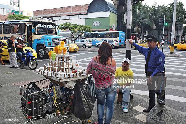 A security guard carrying a machete in an old fashioned way stands on the street corner talking to a vendor in the city center on January 5 2013 in...