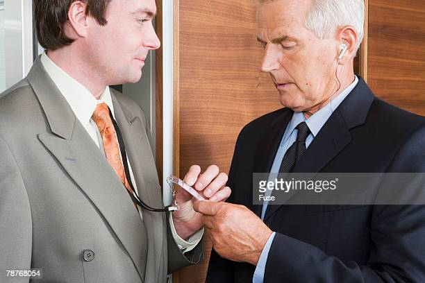Security Guard Checking Businessmans ID Card