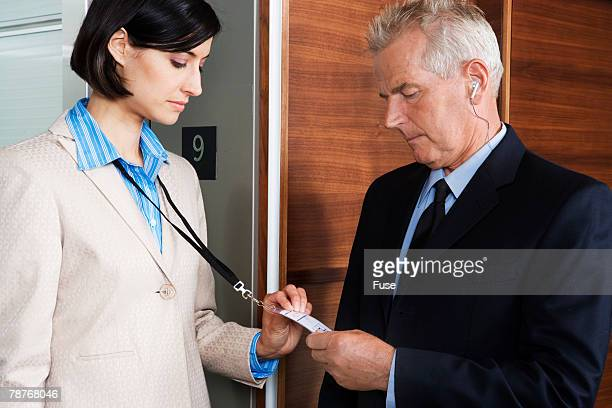 Security Guard Checking Businesswomans ID Card