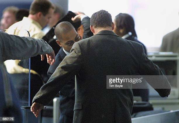 A security guard checks a traveler with a metal detecting handheld wand as he passes through a security checkpoint November 7 2001 in the United...