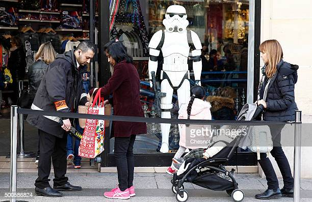 A security guard checks customers in front of the Disney store at 'Champs Elysee' Avenue on December 09 2015 in Paris France Toys from Star Wars...
