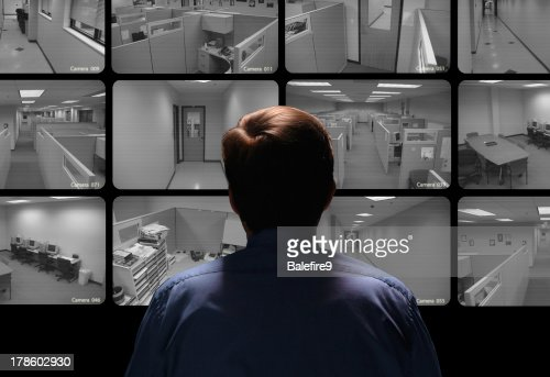 Security guard conducting surveillance by watching several monitors : Stock Photo