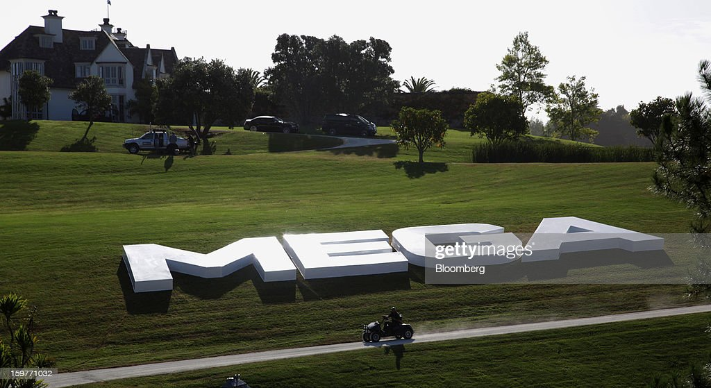 A security guard drives a golf card past Mega signage displayed outside the mansion owned by Kim Dotcom, founder of Megaupload.com, in Coatesville, near Auckland, New Zealand, on Sunday, Jan. 20, 2013. Dotcom, marking one year since his Megaupload.com website was shut down by the U.S. Department of Justice and his home raided by New Zealand tactical squad officers in helicopters, unveiled his new website Mega, a successor file-storage and sharing site, saying innovation won't be stopped. Photographer: Brendon O'Hagan/Bloomberg via Getty Images