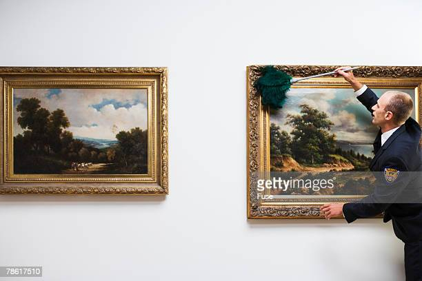 Security Guard Dusting Painting at Art Gallery