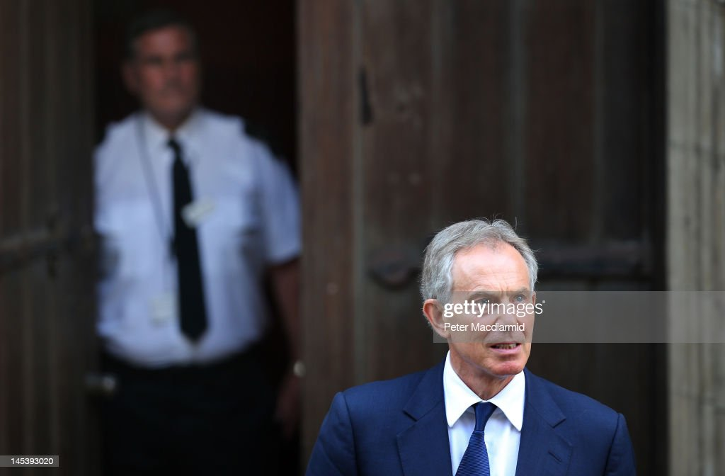 A security guard from the Royal Courts of Justice watches as former Prime Minister Tony Blair leaves by a side door after giving evidence to The...
