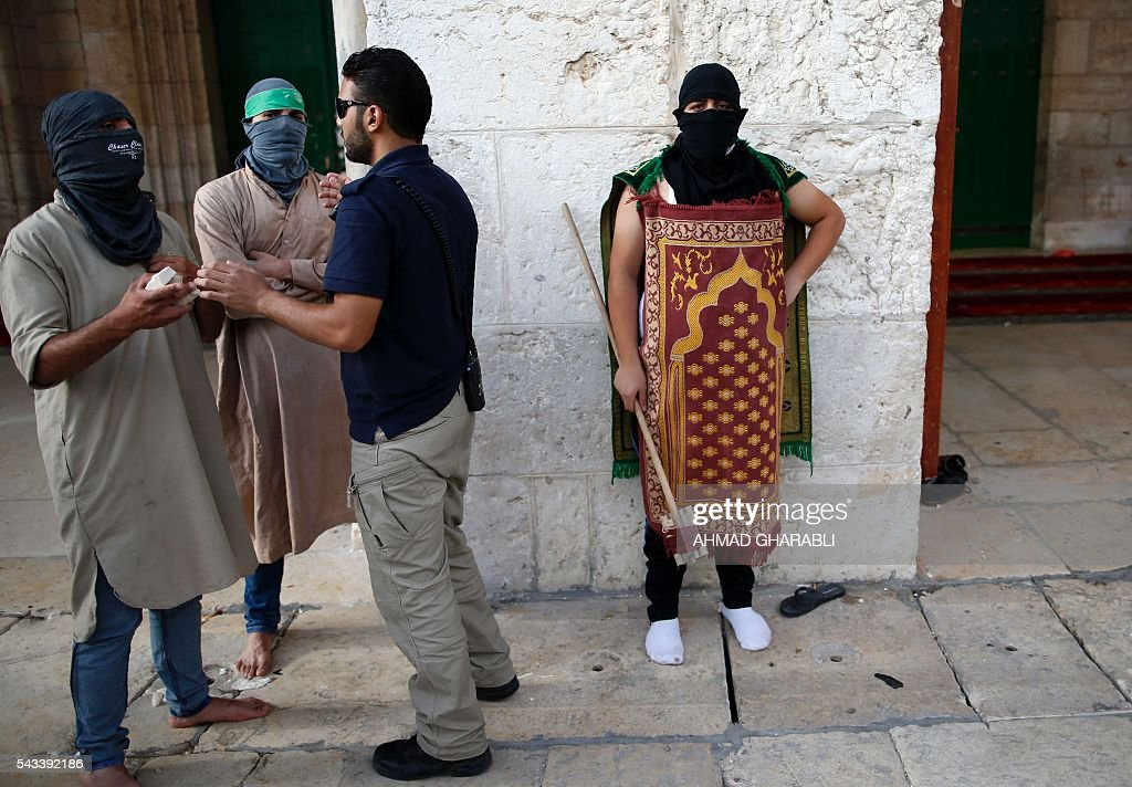A security guard from Waqf, the Jordanian foundation that oversees the Al-Aqsa mosque compound, talks to masked Palestinian protester following clashes with Israeli police at the site on June 28, 2016 in Jerusalem's Old City. Israeli authorities announced they were closing Jerusalem's flashpoint Al-Aqsa mosque compound to non-Muslim visitors after a series of clashes between worshippers and police. The decision will apply until the end of the Muslim holy month of Ramadan next week. / AFP / AHMAD