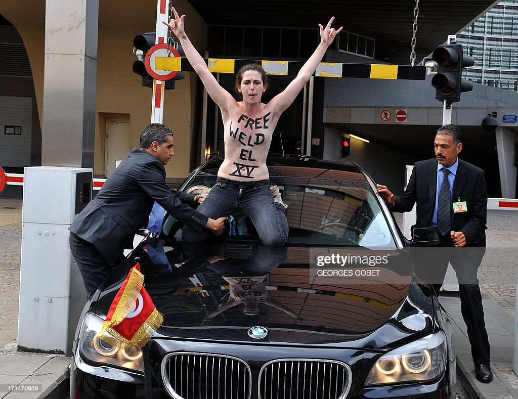 A security guard grabs a Femen activist as she sits on the windshield of Tunisian Prime Minister's car as he leaves the EU commission building after his working session with European Commission President on June 25, 2013 at the EU headquarters in Brussels.