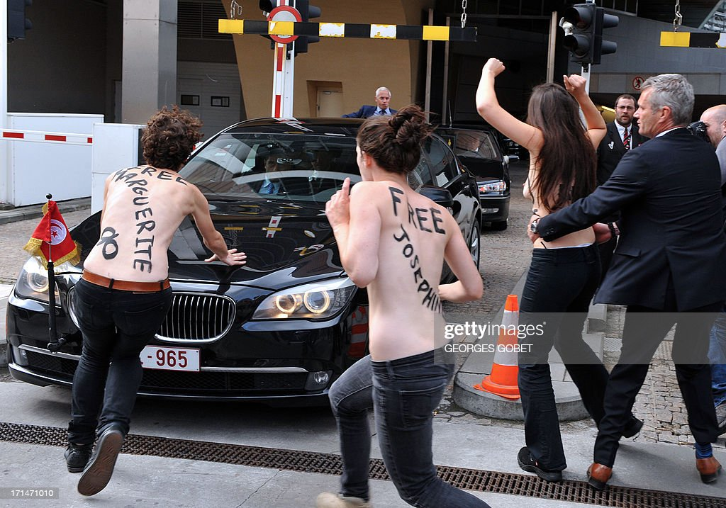 A security guard grabs a Femen activist as she tried along with two other feminist activists to stop the car of Tunisian Prime Minister from leaving the EU commission building after his working session with European Commission President on June 25, 2013 at the EU headquarters in Brussels. The European Commission urged Tunisia to reform criminal laws from its previous authoritarian regime as three topless feminist activists staged a protest by jumping on visiting Tunisian Prime Minister Ali Larayedh's car. Larayedh was visiting Brussels on the eve of an appeals hearing for three European activists from the feminist group Femen who were sentenced to four months in prison this month for baring their breasts in Tunis in a pro-Amina protest.