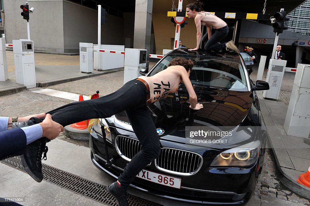 A security guard grabs the leg of a Femen activist as she tried to stop the car of Tunisian Prime Minister from leaving the EU commission building after his working session with European Commission President on June 25, 2013 at the EU headquarters in Brussels.
