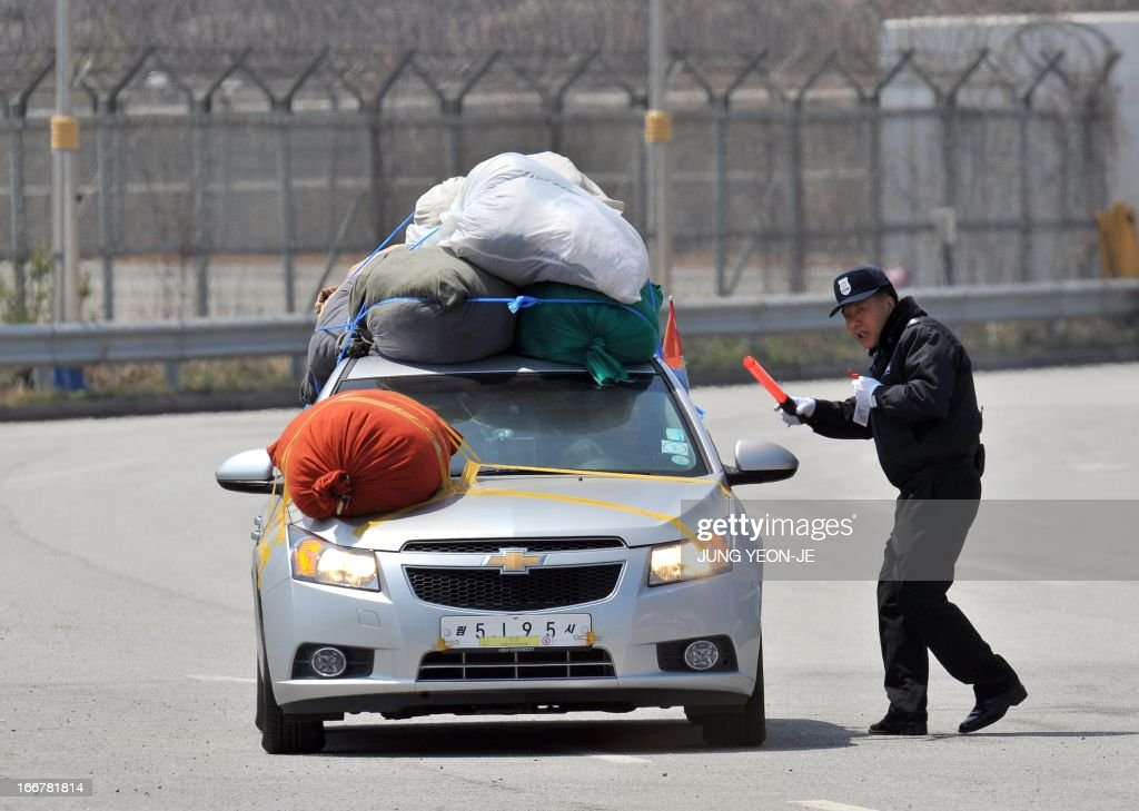 A security guard guides a South Korean car carrying sacks of clothes made in North Korea's Kaesong joint industrial complex, as the car arrives at a gate of the inter-Korean transit office in the border city of Paju on April 17, 2013. North Korea on April 17 ignored the request by South Korean businessmen to cross over the demarcation line that separates the two countries so they can deliver food to employees and check the condition of their facilities at Kaesong.